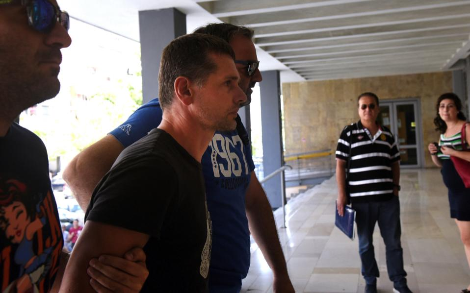 Alexander Vinnik, a 38 year old Russian man (2nd l) suspected of running a money laundering operation, is escorted by plain-clothes police officers to a court in Thessaloniki, Wednesday.