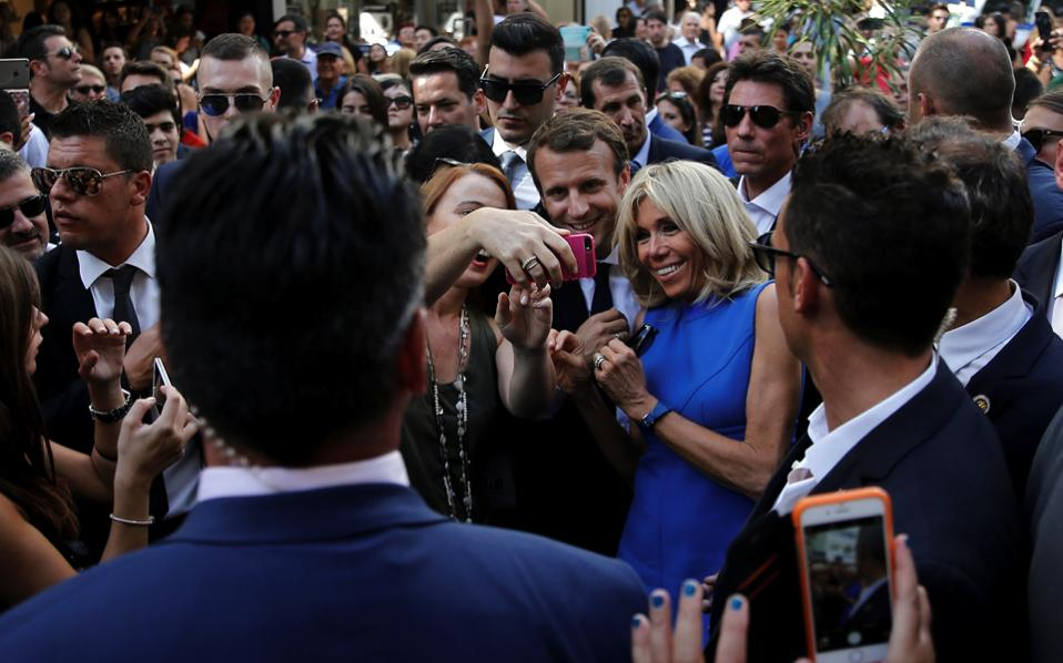 French President Emmanuel Macron and his wife Brigitte Macron take a selfie with passers-by on main commercial Ermou Street in Athens, Friday.