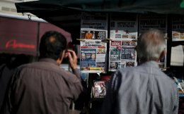 People read newspaper headlines on the German election results at a kiosk in Athens, on Monday.
