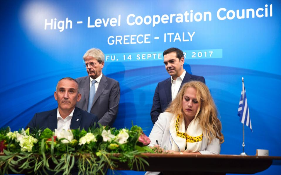 Greek Prime Minister Alexis Tsipras (background right), and his Italian counterpart Paolo Gentiloni (background left), look on as head of Greece's Asset Development Fund Lila Tsitsogianopoulou (r) and Renato Mazzoncini CEO of the Italian Railway holding company Ferrovie dello Stato Italiane, sign a final agreement for the sale of Trainose during the Greek-Italian Intergovernmental Conference at the museum of Asian art in the island of Corfu, Thursday.