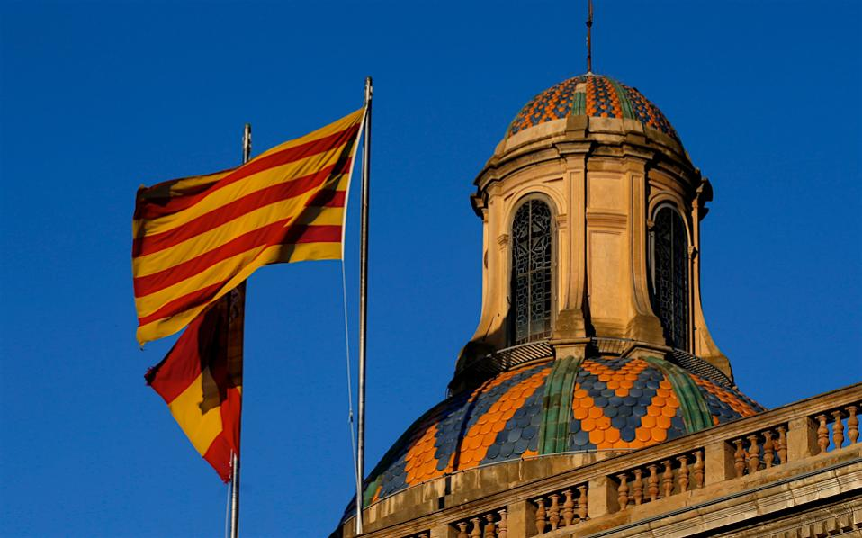 A Catalan and a Spanish flag flutter on top of the Palau Generalitat in Barcelona, Spain, early Monday. Hundreds of thousands of Catalans took to the streets of Barcelona Sunday to call for their region to remain part of Spain, two days after regional lawmakers exacerbated a political crisis by voting for the wealthy region to secede.