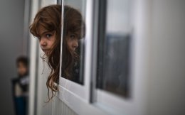An Iraqi girl looks outside her family's shelter at a Greek refugee camp.