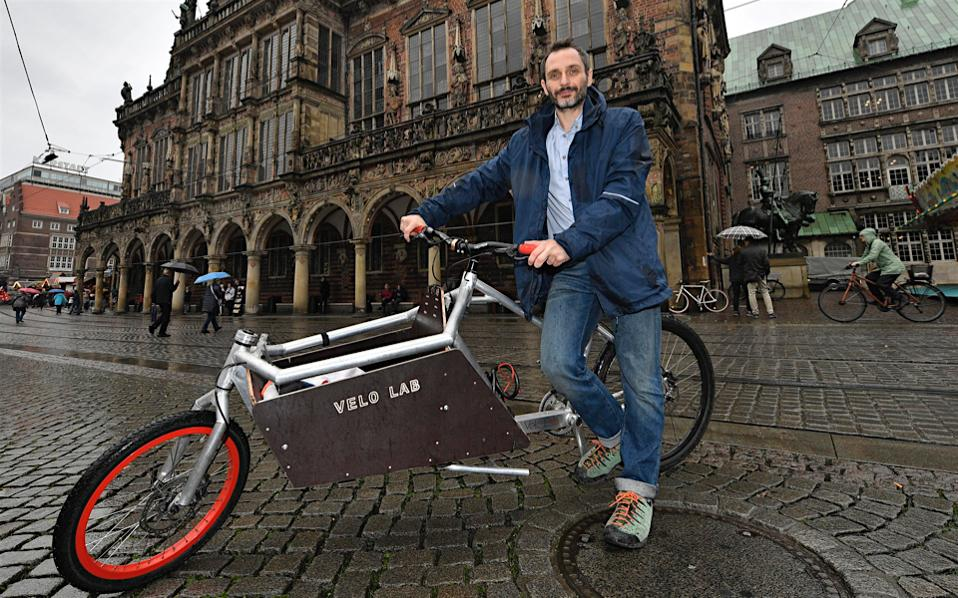 Greek entrepreneur Stathis Stasinopoulos is pictured with a cargo bike in front of the old town hall in Bremen, Germany.