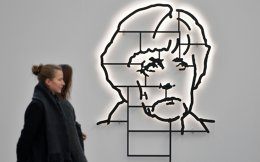 Visitors look at the light sculpture 'It's not Che, it's Angela Merkel' by Cuban artist duo Los Carpinteros on display in the international art fair at Areal Boehler, in Dusseldorf.