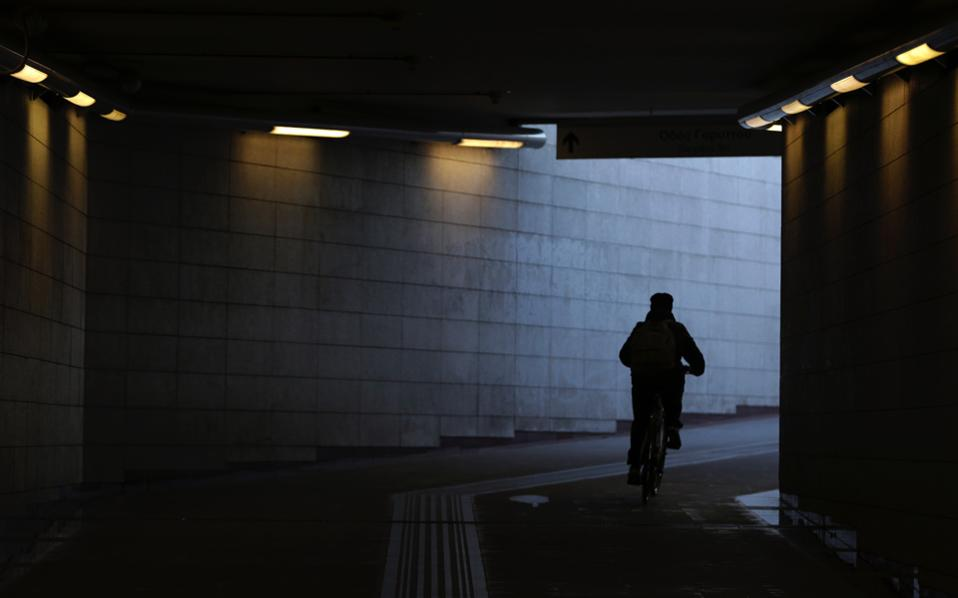 A commuter uses her bicycle to leave from a closed metro station in Athens, Tuesday.