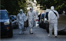 Police experts carry equipment as they search for evidence outside an apartment in the Athens district of Neos Kosmos, on Tuesday.