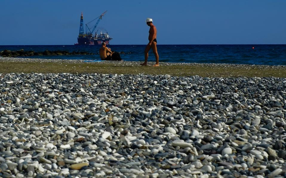 In this photo taken Sunday, Oct. 15, a man walks as an other man sits on a beach during a warm day as a drilling platform is seen in the background, outside from Larnaca port, in the eastern Mediterranean island of Cyprus. The top executive of ENI said Friday that the Italian oil and gas company will drill two exploratory wells off Cyprus in quick succession over the next two months, expressing confidence that significant quantities of the mineral can be found for possible export to energy-hungry Europe.