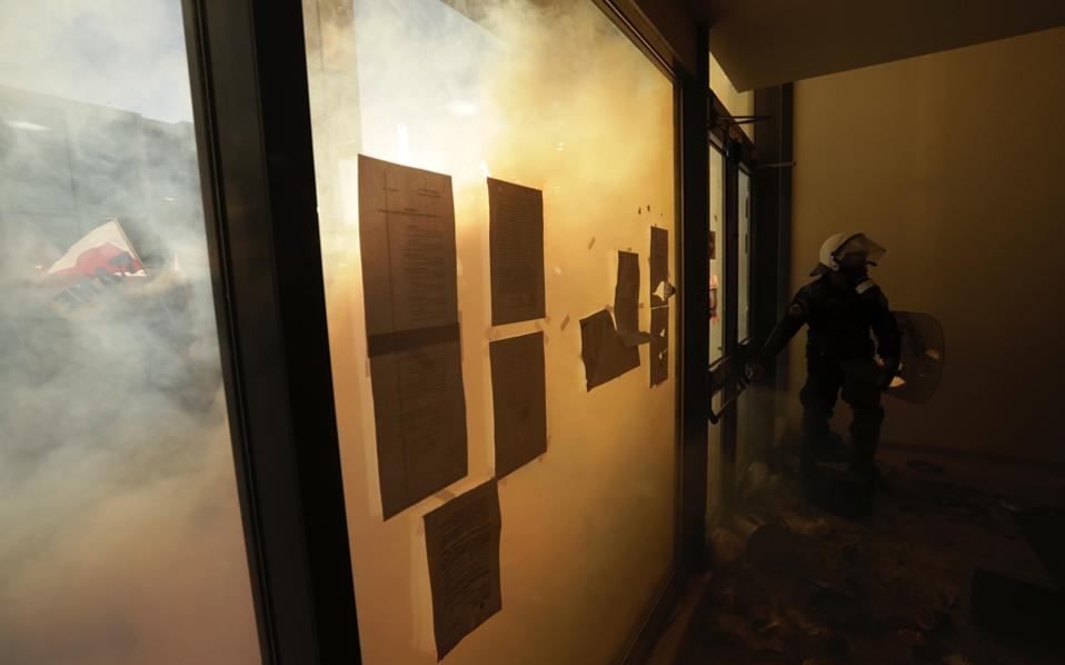 A riot policeman closes the door of the court as protesters try to avoid  tear gas in Athens, on Wednesday. Protesters clashed with police in an Athens court of appeals as foreclosures begin anew as part of reforms under Greece's bailout plans.