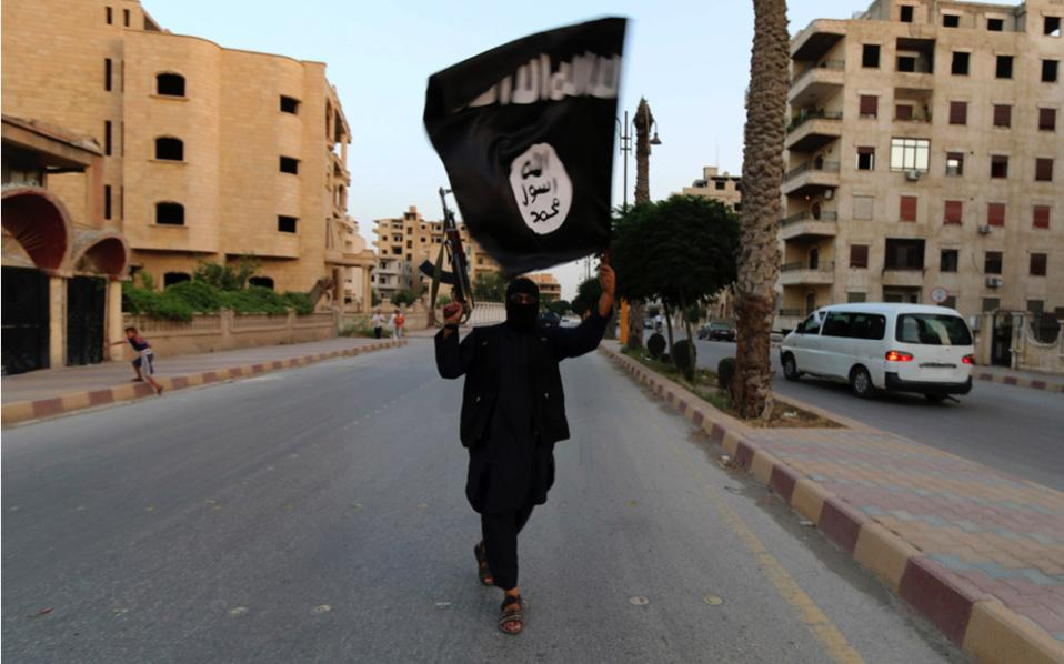 A member loyal to the so-called Islamic State waves an ISIS flag in Raqqa, Syria, in 2014. Islamic extremism is one of the topics that a working group of historians will be adding to the history curriculum of the new education program at Greek schools, Kathimerini has learned.