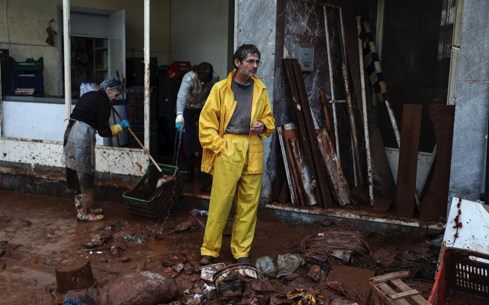 A man stands between debris as two women try to clean a shop from mud at Mandra town, west of Athens, Saturday.