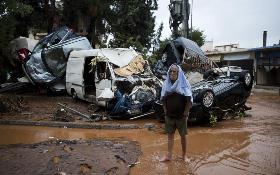In this Wednesday, Nov. 15 photo a barefoot Costas Maroulis 62 stands in front of piled up vehicles in the town of Mandra western Athens, following deadly flash floods that hit the area hours before.