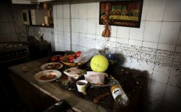 Mud is seen on the kitchen table in the house of Maria Kriada following flash floods which hit areas west of Athens on November 15 killing at least 15 people, in Nea Peramos, Thursday.