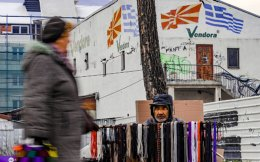 A woman walks past a street vendor selling shoelaces in front of a building with FYROM and Greek flags in Skopje.