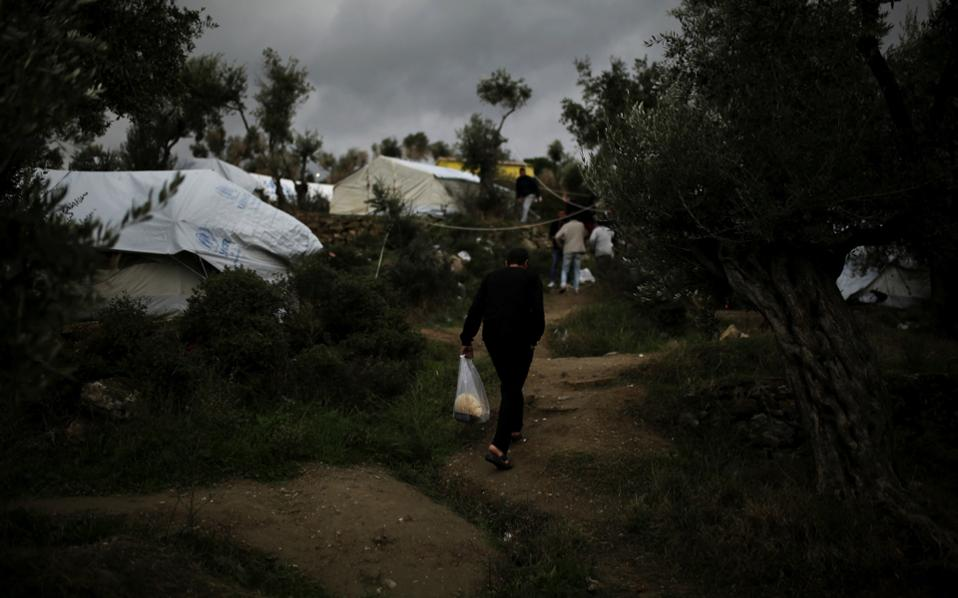 A refugee carries his lunch provided by the Greek authorities, at a makeshift camp for refugees and migrants next to the Moria camp on the island of Lesvos, in a recent photograph.