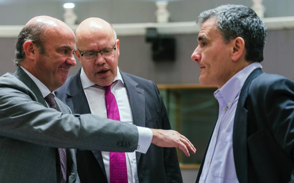 Spain's Finance Minister Luis de Guindos (l), and Germany's acting Finance Minister Peter Altmaier (c), talk with Greece's Finance Minister Euclid Tsakalotos during a Eurogroup finance ministers meeting at the EU Council in Brussels on Monday.