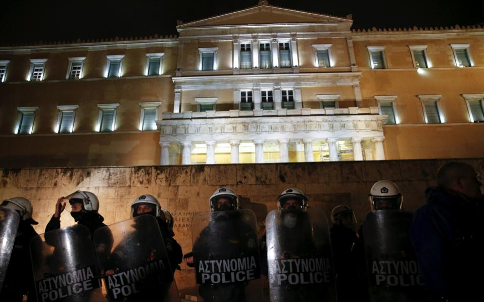 Riot police officers stand guard in front of the parliament building during a demonstration against planned government reforms late Monday.