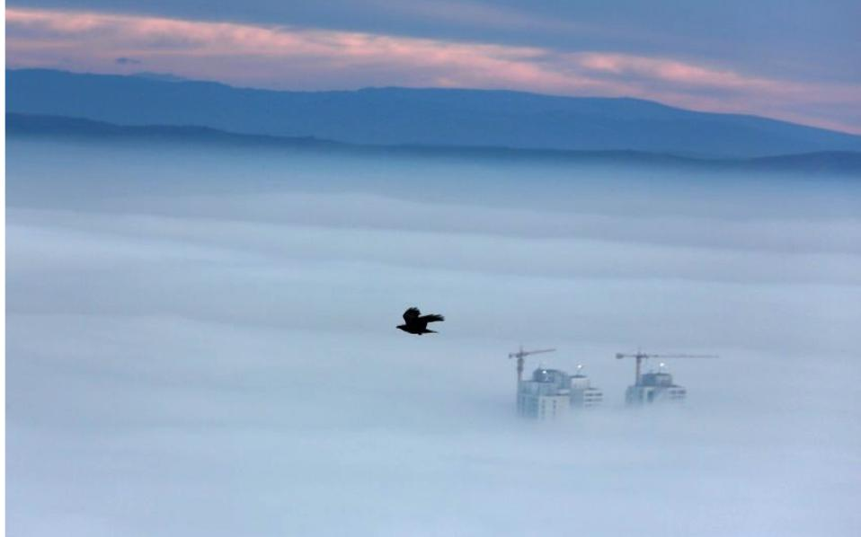 Buildings are seen as fog blankets the city of Skopje, capital of the Former Yugoslav Republic of Macedonia (FYROM). Many people wonder why the name issue reappeared all of a sudden. The answer lies in the geopolitical game that is being played out in the Western Balkans.