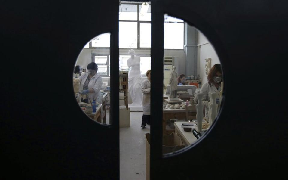 Employees of Culture Ministry work in their lab in Athens. [Thanassis Stavrakis/AP]