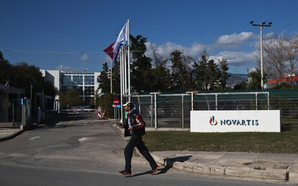 A man crosses the street outside the Novartis Greek offices in Athens, on Tuesday.