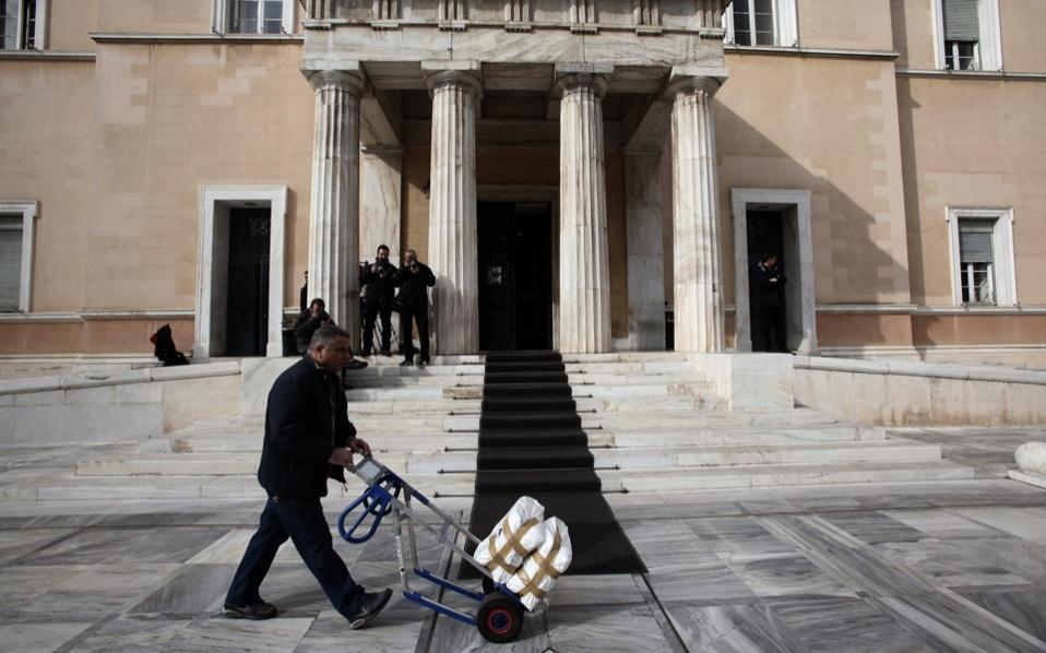 A Parliament employee wheels documents into the House where leftist SYRIZA's political council met on Wednesday under Prime Minister Alexis Tsipras.
