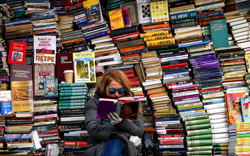 A street bookseller reads a book at a stall at the main square of FYROM capital Skopje.