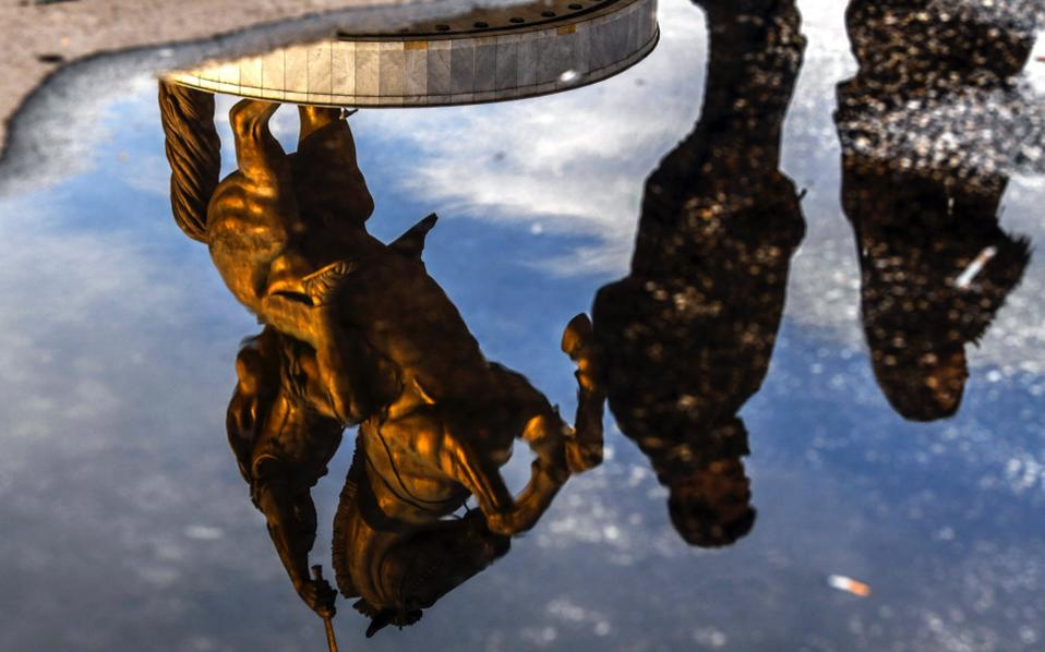 People walk next to the reflection of a monument called 'Warrior on the horse,' at the main square of the capital Skopje.