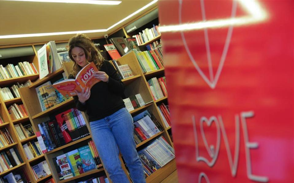A woman looks for a book at a bookstore in the Athens northern suburb of Kifissia, on Wednesday, to celebrate Valentine's Day.