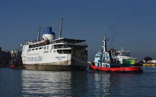partially-sunken-ship-towed-out-of-piraeus-port