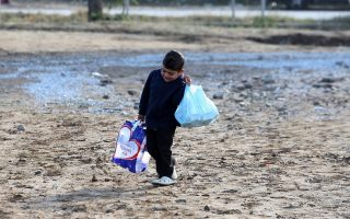 young-refugee-carries-supplies-through-muddy-camp