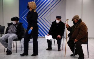 A medical staff walks among elderly men waiting to receive a dose of Moderna COVID-19 vaccine at the vaccination mega center in Athens, Monday, February 15, 2021. The Promitheas center, which has started operating Monday, will host 96 vaccination points and when fully developed, an estimated of 150,000 vaccinations per month could be conducted. [Thanassis Stavrakis/AP]