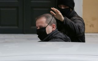 Greek actor and former director of Greece's National Theatre Dimitris Lignadis enters a car as he leaves prosecutor's office escorted by plain clothes police officers in Athens, Greece, February 21, 2021. [Costas Baltas/Reuters]