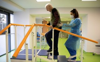 Yannis Ieremias, 70, is assisted by physiotherapist Georgia Bahou at the Theseus Rehabilitation Centre in Athens, Greece, February 1, 2021. [Alkis Konstantinidis/Reuters]