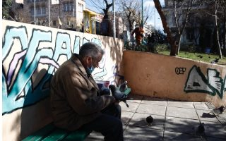 An elderly man feeds the pigeons in a public square in downtown Thessaloniki, northern Greece, in January. As the long winter of the pandemic drags on, we should all try to look after one another. [Dimitris Tosidis/ANA-MPA]
