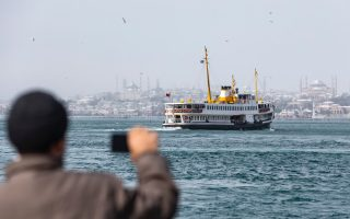 A man takes a photograph from the bank of the Bosphorus on a snowy day in Istanbul on Tuesday. [Erdem/Sahin/EPA]