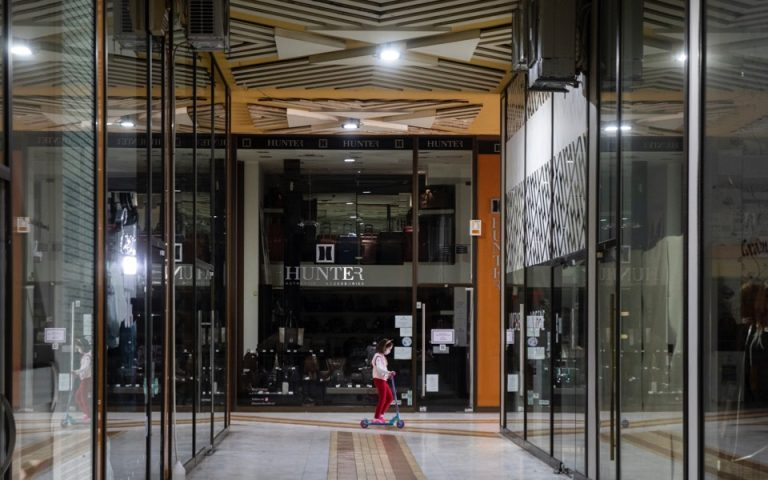 A girl rides a scooter inside a mall with closed shops, in the suburb of Glyfada, south of Athens, earlier this month. [AP]