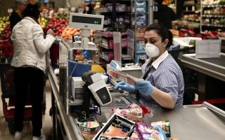 A checkout worker wears a mask and gloves to protect herself from Covid-19 at an Athens supermarket in this March 2020 file photo. Ian Bremmer notes that the virus has disproportionately hit the earnings of low-income and service workers. [InTime News]