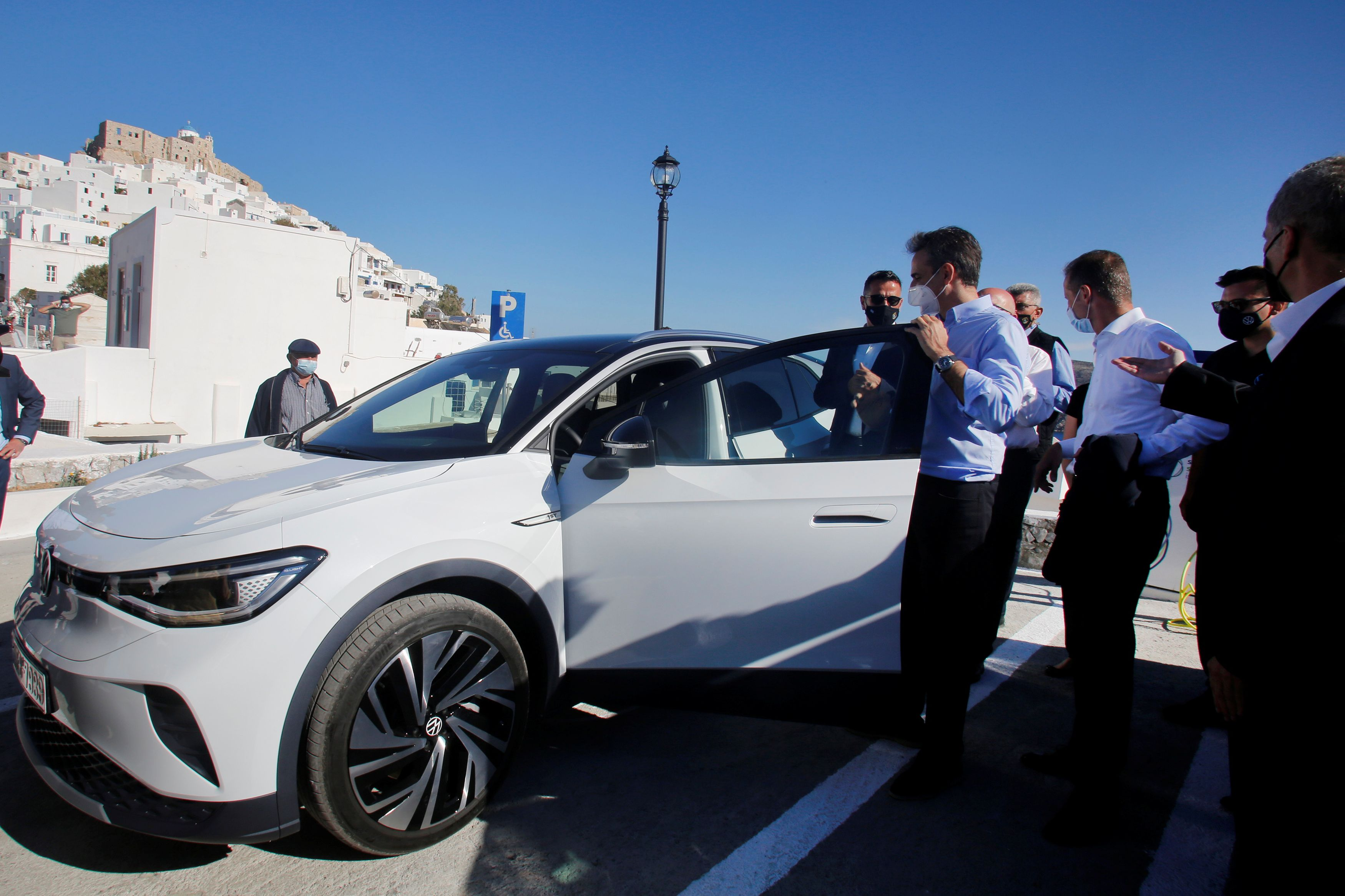 Greek Prime Minister Kyriakos Mitsotakis looks at a Volkswagen ID.4 electric car, during a delivery ceremony of service cars and chargers to the police and the port authority of the island of Astypalea, Greece, June 2, 2021. [Alexandros Vlachos/Pool via Reuters]